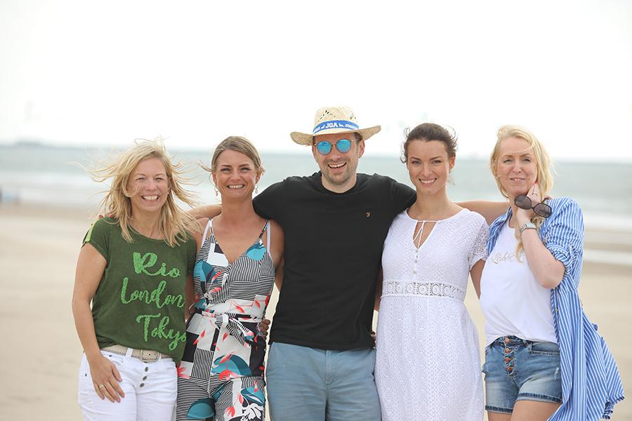 Ein Mann und vier Frauen stehen Arm in Arm am Strand von Wijk aan Zee