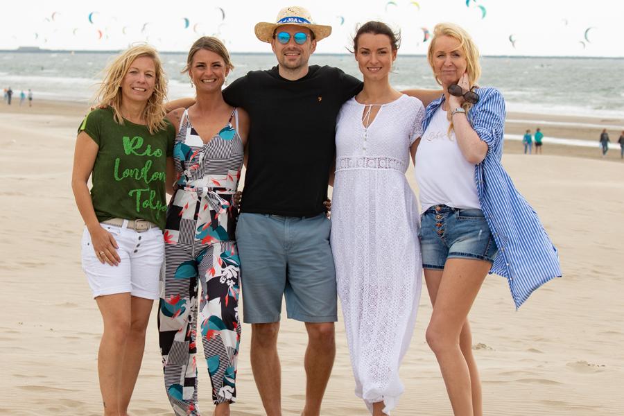 Ein Mann und vier Drauen stehen am Strand in Wijk aan Zee