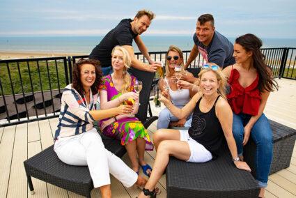 Glückliche Gruppe auf einer Terasse mit Meerblick in Wijk aan Zee