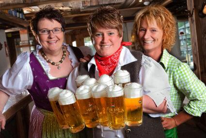 Drei Frauen in Tracht mit viel Bier im Hotel Dorf Alm in Willingen
