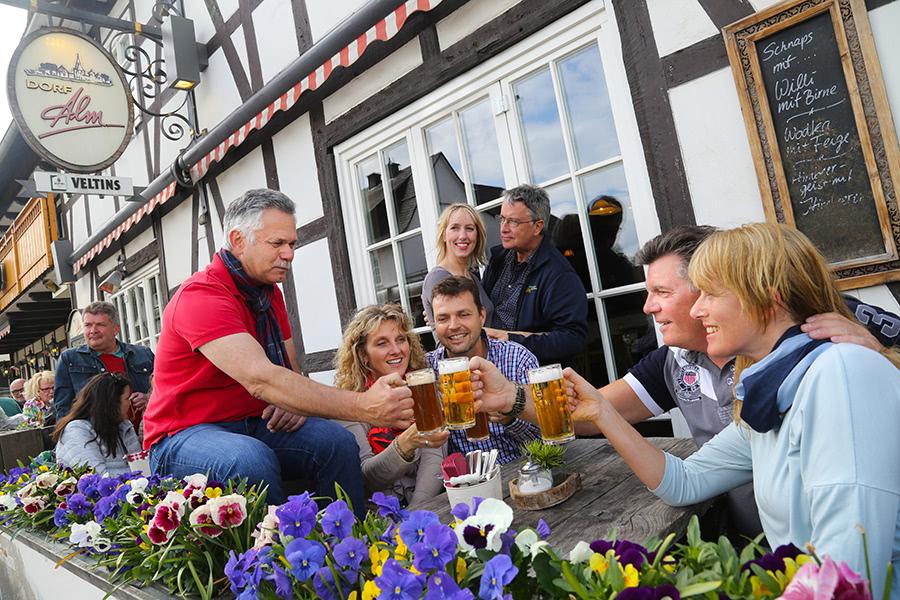 Gruppe trinkt gemeinsam Bier auf der Terasse vom Hotel Dorf Alm Willingen