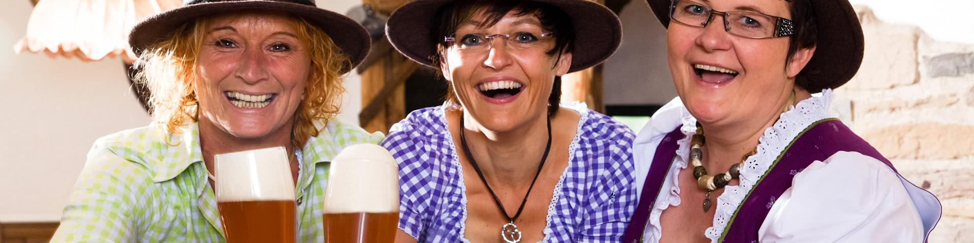 Drei Frauen in Tracht trinken Bier in der Dorf Alm in Willingen