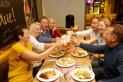 Gruppe isst gemeinsam zu Abend und stößt mit Bier an im Brauhaus in Willingen