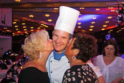 Zwei Frauen Küssen einen Koch auf die Wangen beim Abschlussfest in Willingen