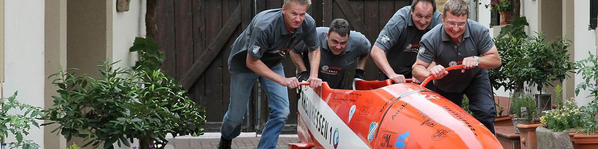 Vier Männer schieben einen Sommerbob in Winterberg